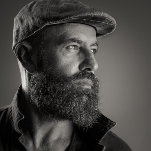 man with beard and flat cap