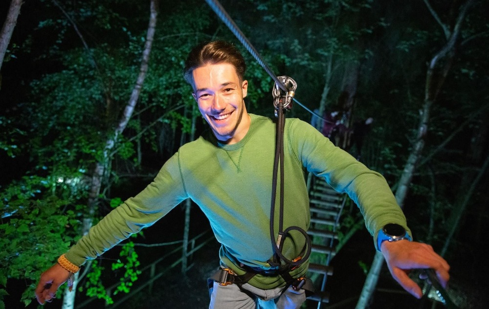 man on a zip line in the dark