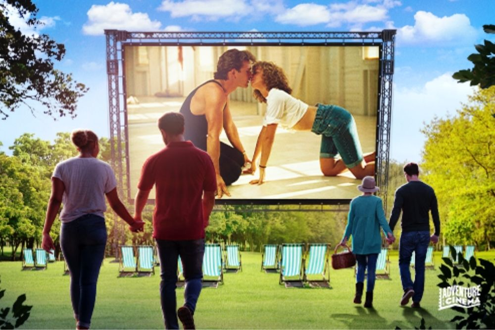 An artist's impression of two couples watching Dirty Dancing on a large screen.