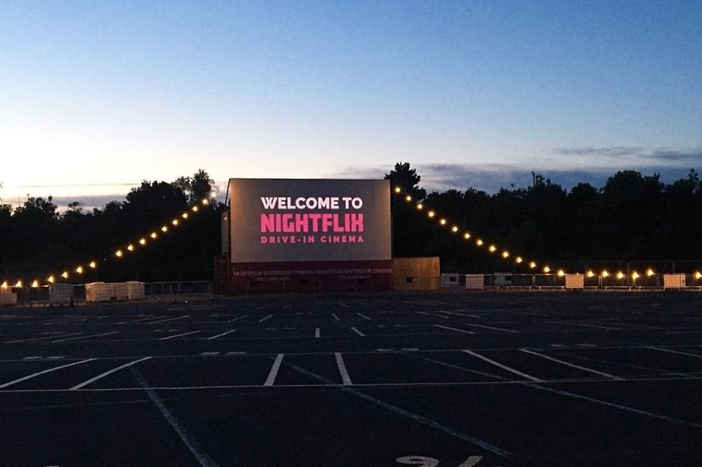 A big screen by an empty car park reads 'welcome to nightflix'