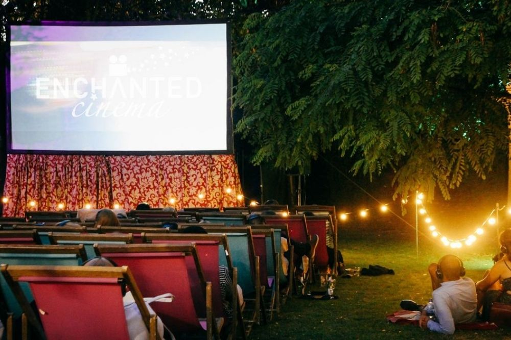 A couple watch an outdoor cinema screen, on which is written Enchanted Cinema