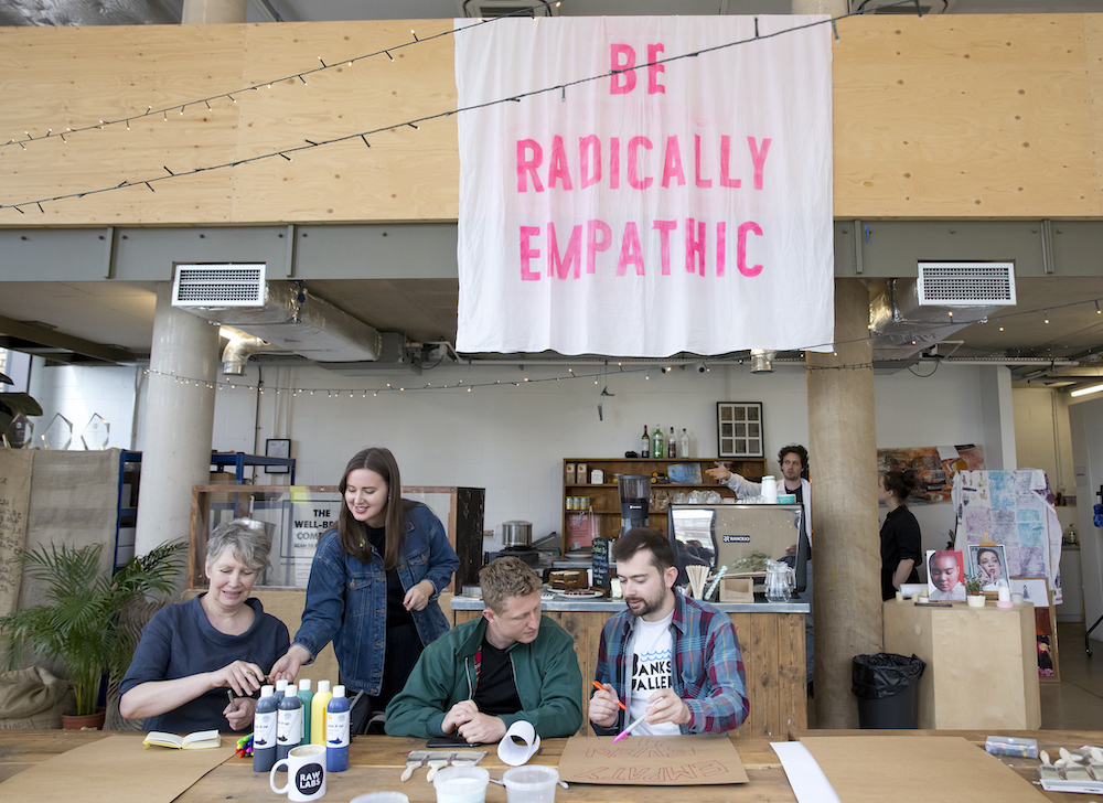 A sign says 'be radically empathetic', below which people work on art.