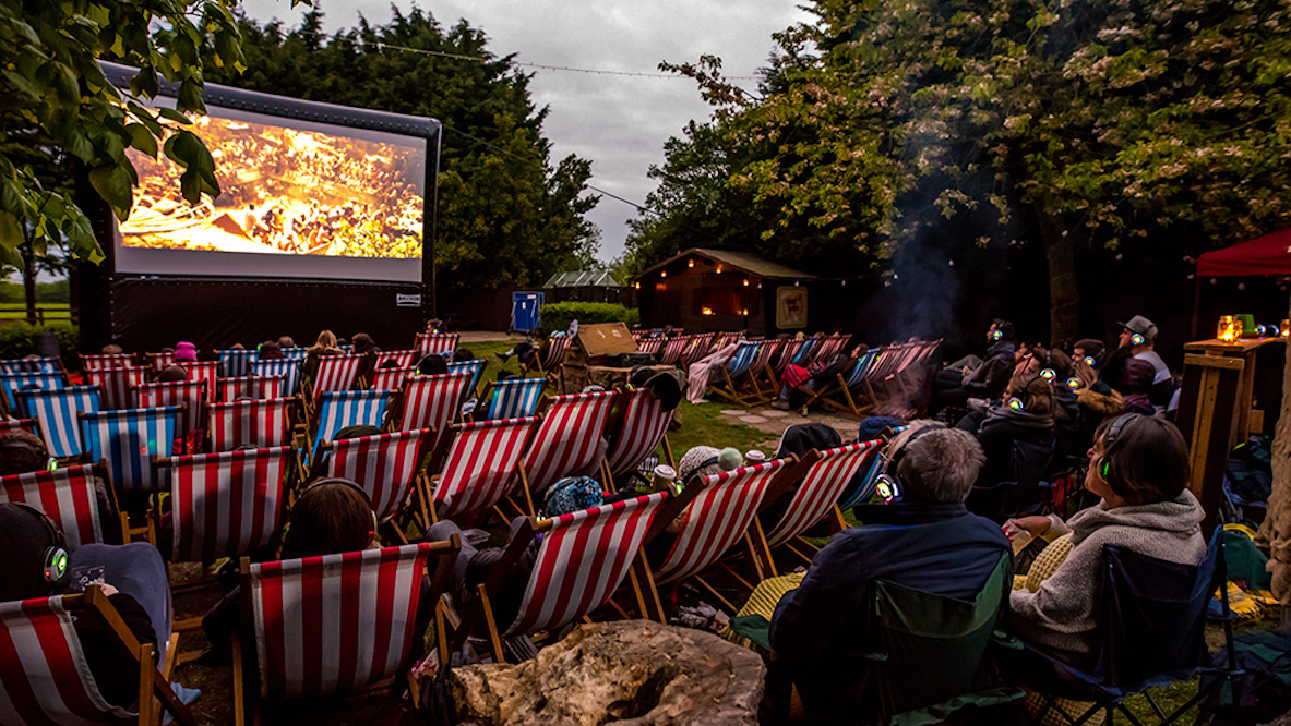 People sit on striped deckchairs watching a film